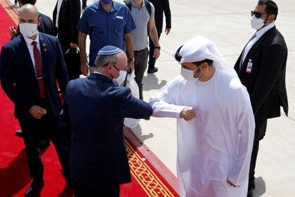 El asesor de seguridad nacional israelí Meir Ben-Shabbat se codea con un funcionario de los Emiratos Árabes Unidos mientras se dirige a abordar el avión que saldrá de Abu Dhabi, Emiratos Árabes Unidos, el 1 de septiembre de 2020 (REUTERS/Nir Elias//Archivo Foto)