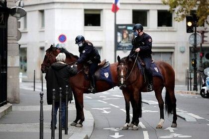 FOTO DE ARCHIVO: Oficiales de policía a caballo realizan un control a un transeúnte en la avenida Champs-Elysee, en París, el 31 de octubre de 2020. REUTERS/Benoit Tessier