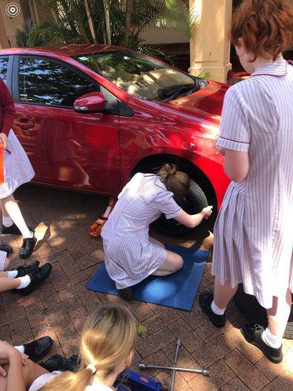 Una de las alumnas en plena tarea de cambio de un neumático