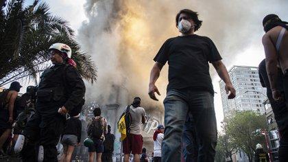 La gente es vista afuera de la iglesia en llamas de Asunción después de que fue incendiada por manifestantes en la conmemoración del primer aniversario del levantamiento social en Chile, en Santiago, el 18 de octubre de 2020, mientras el país se prepara para un referéndum histórico. (Photo by MARTIN BERNETTI / AFP)