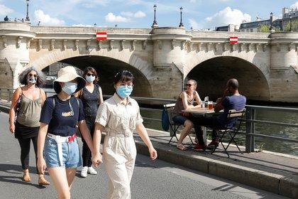 Peatones con máscaras protectoras caminan a lo largo de las orillas del río Sena en París el 15 de agosto de 2020, mientras Francia refuerza el uso de máscaras como parte de los esfuerzos para frenar el resurgimiento de la enfermedad coronavirus (COVID-19) en todo el país (REUTERS/Charles Platiau)