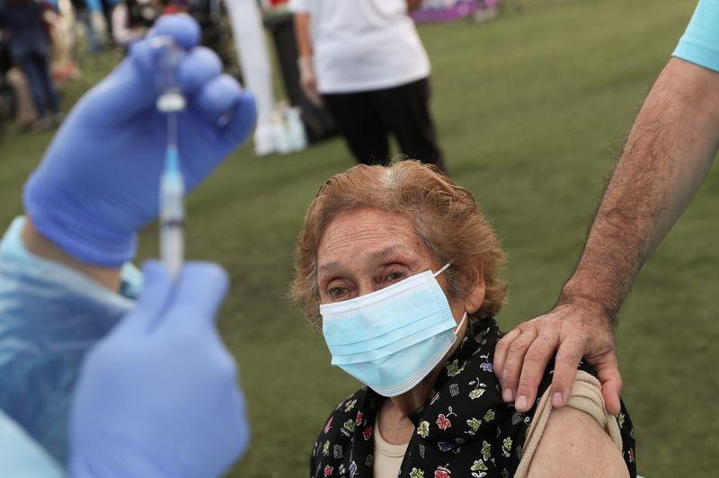 Una trabajadora de la salud se prepara para administrar una dosis de la vacuna CoronaVac de Sinovac contra el coronavirus a una anciana en Santiago, Chile. 3 febrero 2021. REUTERS/Ivan Alvarado
