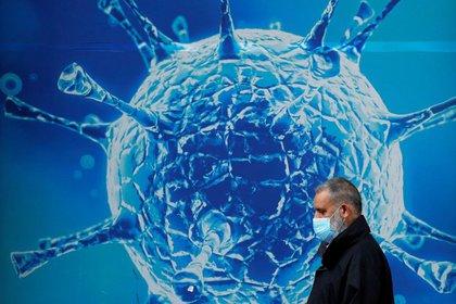 IMAGEN DE ARCHIVO. Un hombre utilizando una mascarilla camina cerca de una ilustración de un virus fuera  de un centro regional de ciencia en Oldham, Gran Bretaña. Agosto 3, 2020. REUTERS/Phil Noble