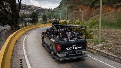 Agentes de las Fuerzas Armadas Bolivarianas cruzan en una camioneta hacia el lugar donde se realiza una operación contra el grupo liderado por el policía Óscar Pérez en el barrio El Junquito, en Caracas (Venezuela)