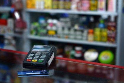 En la imagen, un punto de pago junto a una tarjeta de crédito. EFE/Oskar Burgos/Archivo