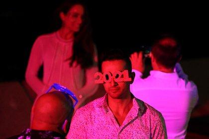 Un hombre con anteojos con forma de 2021 aguarda que comiencen los fuegos artificiales en el puerto de Sídney, Australia (Reuters/ Loren Elliott)