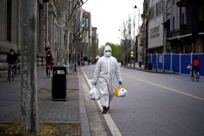 Un hombre con un traje de protección camina por una calle en Wuhan, provincia de Hubei, el epicentro del brote de coronavirus (COVID-19) en China , el 28 de marzo, 2020. REUTERS/Aly Song