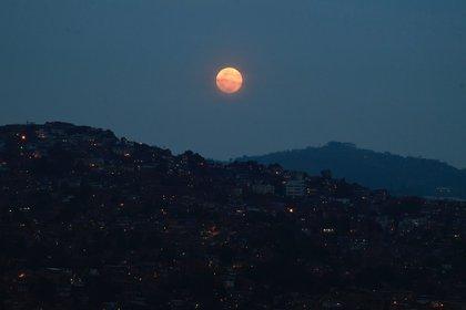 """La """"Super Luna Rosa"""" llena se ve sobre el barrio de Petare en Caracas, el 26 de abril de 2021 (Photo by Federico Parra / AFP)"""