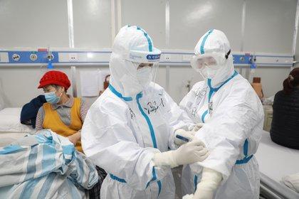 Un trabajador médico anota información de un paciente en Wuhan (China Daily via REUTERS)