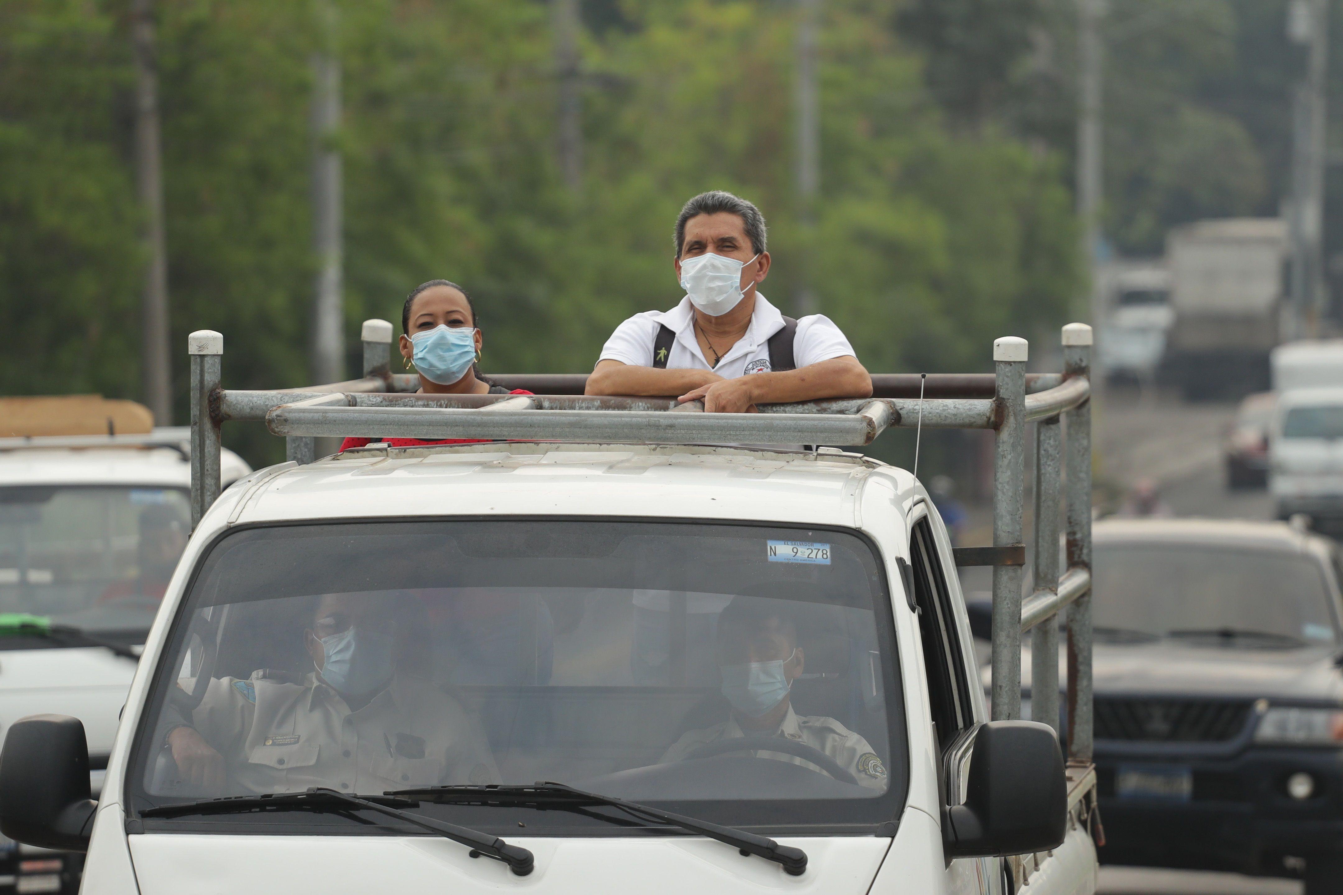 Dos personas con tapabocas viajan este jueves sobre el platón de una camioneta, en San Salvador (El Salvador). EFE/Rodrigo Sura/Archivo