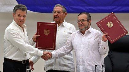 Durante la firma del acuerdo de paz, el presidente Juan Manuel Santos y el exguerrillero de las FARC alias Timochenko. (EFE)