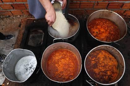 El cocinero Walter Ferreira vierte arroz en un estofado en un comedor social en Luque, Paraguay, el lunes 11 de mayo de 2020. El número de comedores benéficos en el país se ha multiplicado, después de que la cuarentena contra la pandemia de coronavirus paralizara la economía del país. (AP Foto/Jorge Saenz)