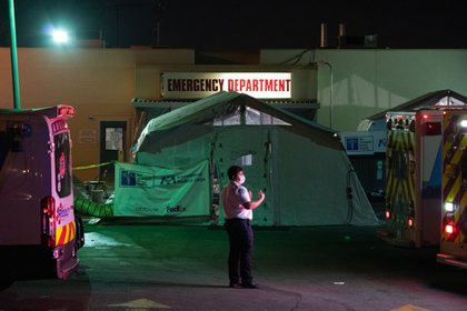 An emergency medical technician (EMT) directs an ambulance outside the emergency room of the East Los Angeles Doctors Hospital in Los Angeles, California, U.S., on Wednesday, Jan. 6, 2021. California reported 459 daily virus deaths, the second-highest tally since the pandemic began, as the most-populous state continues to battle a surge of cases that has strained health-care facilities.