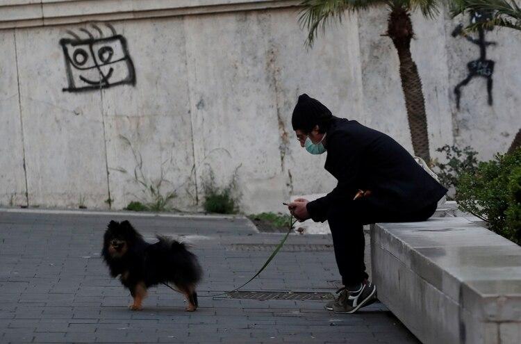 Un hombre con barbijo pasea a su perro en Nápoles (REUTERS/Ciro De Luca)