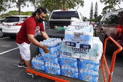 Un hombre carga botellas de agua en Lantana Costco este 1 de agosto antes de que el huracán tropical Isaias toque tierra en Florida. (Damon Higgins/Palm Beach Post via ZUMA Wire/dpa)