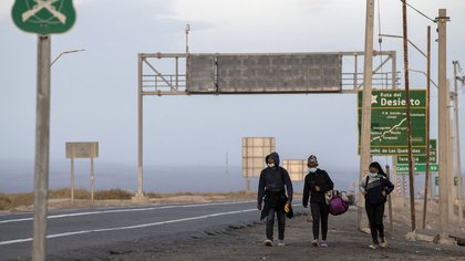 Venezuelan migrants Reinaldo (L), 26, Anyier (C), 40, and her daughter Danyierly, 14, walk along the highway on their way to Iquique, after crossing from Bolivia, in Colchane, Chile, on February 18, 2021. - Crossing the highlands of the border between Bolivia and Chile on foot is the hardest part of the journey Venezuelan migrants go through on their way to Iquique or Santiago. (Photo by Martin BERNETTI / AFP)