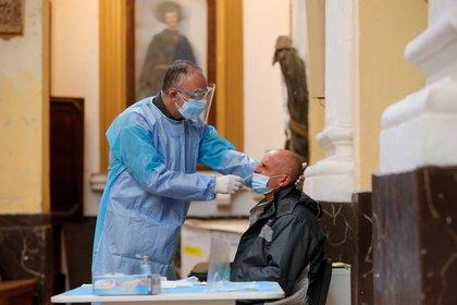 Un miembro del personal médico que lleva ropa de protección toma una muestra de un hombre en el centro de pruebas de la enfermedad coronavirus (COVID-19) en la iglesia de San Severo fuori le mura, en Nápoles, Italia, el 18 de noviembre de 2020. REUTERS/Ciro De Luca