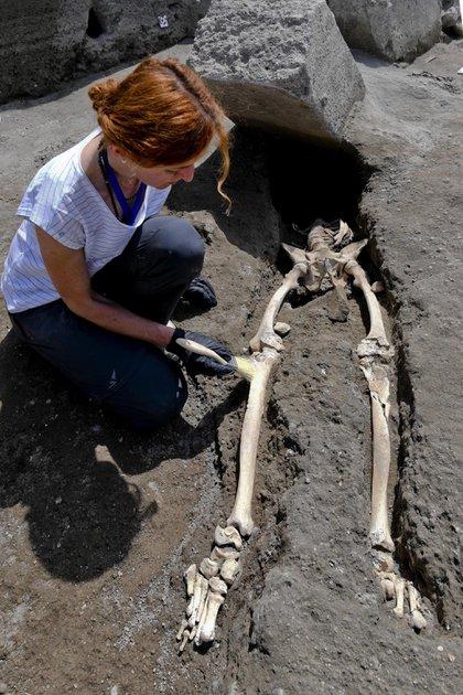 Una antropóloga examina los restos óseos de un nuevo esqueleto (EFE/ Ciro Fusco)