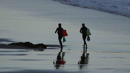 Dos surfistas en la playa vizcaína de Sopelana se dirigen a realizar surf (EFE/LUIS TEJIDO)