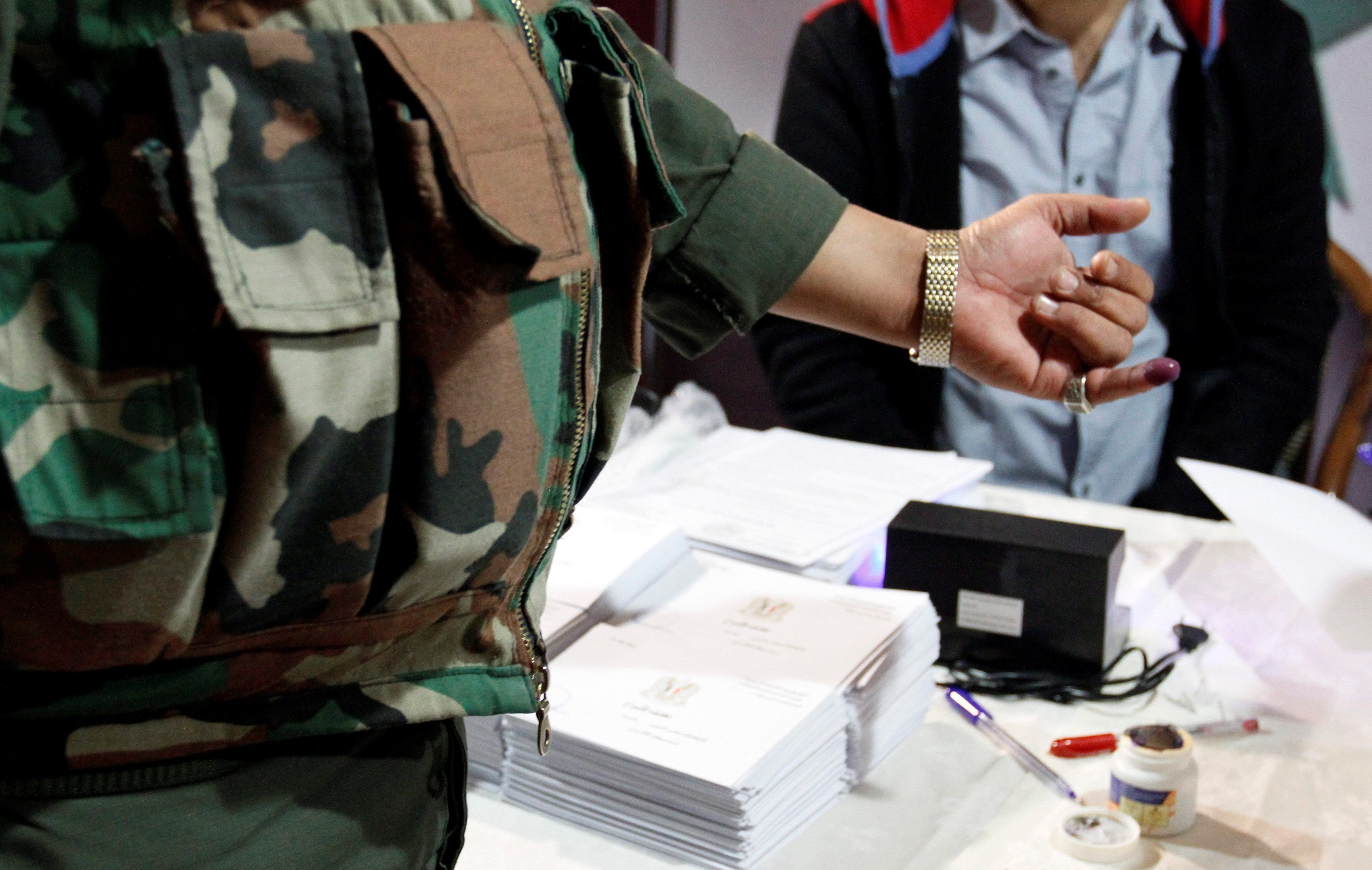 Un soldado mancha su dedo en tinta tras ejercer su derecho al voto en un colegio electoral en Damasco (Siria). EFE/Youssef Badawi/Archivo