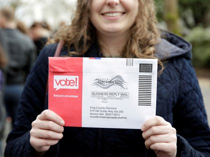 FILE PHOTO: Lexi Menth of Seattle holds up her vote-by-mail ballot as supporters line up at a rally for U.S. Democratic 2020 presidential candidate Senator Elizabeth Warren at the Seattle Center Armory in Seattle, Washington, U.S. February 22, 2020. REUTERS/Jason Redmond - RC206F95RLJN/File Photo