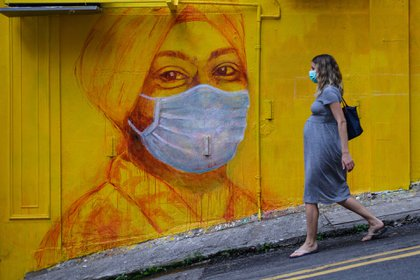 Una mujer embarazada pasa frente a un mural callejero en Hong Kong.