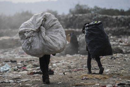 """Los recolectores llevan bolsas en el basurero """"Bordo de Xochiaca"""" en Ciudad Nezahualcóyotl, Estado de México el 21 de julio de 2020, en medio de la nueva pandemia de coronavirus. (Foto por PEDRO PARDO / AFP)"""