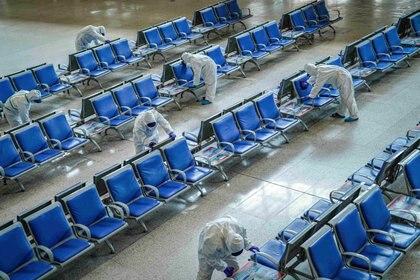 Trabajadores desinfectan la sala de espera de una estación de tren en Wuhan, China, donde surgió la enfermedad (REUTERS)