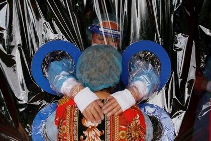 """Arcelia Aguilar, residente del """"Hogar Jardín De Los Abuelitos"""", recibe un abrazo de su sobrina María Aguilar a través de """"El muro de los Abrazos"""" que es una pared hecha con láminas de plástico para protegerse del potencial coronavirus, en San Salvador, El Salvador (REUTERS/Jose Cabezas)"""