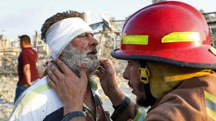 Un bombero atiende a una persona herida en la explosión (AFP)
