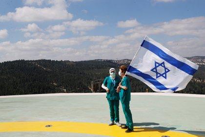 Médicos posan con banderas de israel en el hospital Hadassah Ein Kerem en Jerusalem, como apoyo al gobierno y al personal médico. REUTERS/Ronen Zvulun