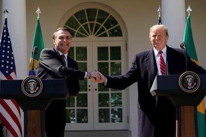 El presidente de Brasil, Jair Bolsonaro, se da la mano con su par estadounidense, Donald Trump, en una conferencia de prensa conjunta en el Rose Garden de la Casa Blanca en Washington. 19 de marzo de 2019. REUTERS/Kevin Lamarque.