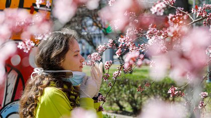 A girl removes the mask to smell the flowers on a blooming tree following the outbreak of the coronavirus disease (COVID-19) in Skopje, North Macedonia March 20, 2020. REUTERS/Ognen Teofilovski
