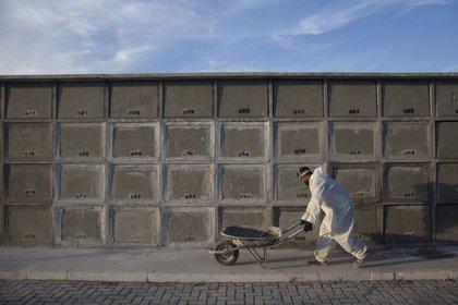 Un trabajador vestido con un traje especial de protección pasa frente a nichos funerarios de construcción reciente en el cementerio público de la ciudad de Duque de Caxias, Brasil