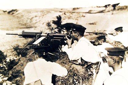 Soldados japoneses con uniformes blancos y gorras de vestir posan detrás de una ametralladora pesada en una foto sin fecha capturada por los Marines de los Estados Unidos durante la Batalla de Guadalcanal de la Segunda Guerra Mundial en las Islas Salomón en febrero de 1943.  U.S. Navy/Handout via REUTERS/File Photo