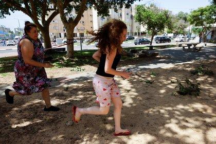 Una mujer y un adolescente corren mientras suena una sirena advirtiendo de un cohete entrante lanzado desde la Franja de Gaza, en Ashkelon (REUTERS / Amir Cohen)