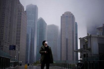 Un hombre con una máscara facial protectora en en el distrito financiero de Lujiazui en Shanghái, China, el 13 de marzo de 2020. REUTERS/Aly Song