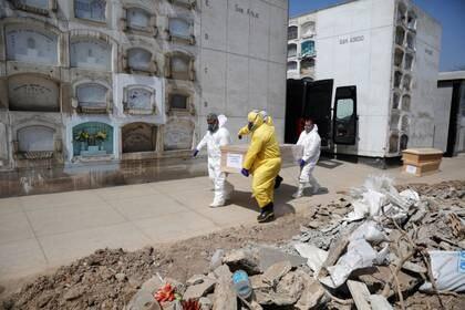 Trabajadores funerarios trasladan un atúd con el cuerpo de una persona fallecida por COVID-19, en un cementerio en Lima, Perú. 9 de mayo de  2020 (REUTERS/Sebastian Castaneda)