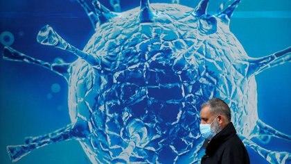 Hombre con mascarilla pasa junto a una ilustración de virus fuera de un centro científico regional, Oldham, Gran Bretaña, 3 agosto 2020. REUTERS/Phil Noble/Files
