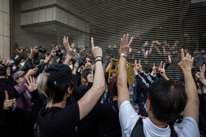 Activistas pro-democracia sostienen pancartas en apoyo a compañeros activistas arrestados fuera de la Corte de Kowloon Occidental en Hong Kong, China, el 1 de marzo de 2021 (EFE/EPA/ JEROME FAVRE)