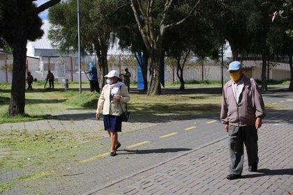 Una pareja de jubilados camina este martes por la avenida Río Amazonas y mantenien la distancia de bioseguridad que recomiendan las autoridades en Quito. EFE/Elías L. Benarroch