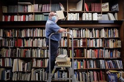 El librero Philippe Seyrat, usando una mascarilla, ordena libros en la tienda La Sorbonne en Niza luego de que Francia flexibilizó las estrictas normas de confinamiento durante la pandemia de COVID-19, la enfermedad causada por el coronavirus (REUTERS/Eric Gaillard)