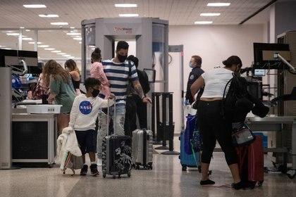 Una familia usa mascarillas al pasar la seguridad en la Terminal A del Aeropuerto Intercontinental George Bush en medio del brote de la enfermedad coronavirus (COVID-19) en Houston, Texas, Estados Unidos (REUTERS/Adrees Latif)