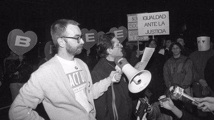 Jáuregui con el megáfono. A la derecha, manifestantes con sus caras cubiertas con máscaras de papel