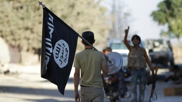Un rebelde lleva como trofeo una bandera del Estado Islámico (Reuters)