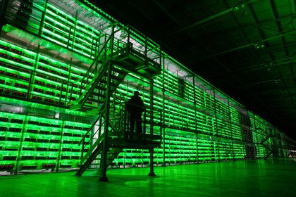 An armed guard patrols in front of illuminated mining rigs mounted inside racks at the BitRiver Rus LLC cryptocurrency mining farm in Bratsk, Russia, on Friday, Nov. 8, 2019. Bitriver, the largest data center in the former Soviet Union, was opened just a year ago, but has already won clients from all over the world, including the U.S., Japan and China. Most of them mine bitcoins. Photographer: Andrey Rudakov/Bloomberg
