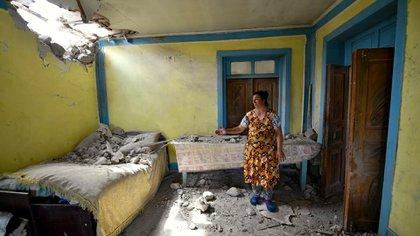 Una residente de la región de Tovuz, el Azerbaiyán, muestra los daños producidos en su casa por parte de la artillería armenia. (AP Photo/Ramil Zeynalov)