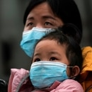 A woman wearing a face mask holds a child as they arrive at a railway station in Wuhan on the first day inbound train services resumed following the novel coronavirus disease (COVID-19) outbreak, in Wuhan of Hubei province, the epicentre of China's coronavirus outbreak, March 28, 2020. REUTERS/Aly Song