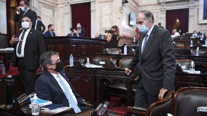 Los senadores del interbloque de Juntos por el Cambio Víctor Zimmermann -de pie- y Luis Naidenoff conversan antes de que empiece a hablar el jefe del Ejecutivo Nacional en el Congreso. (Comunicación Senado).