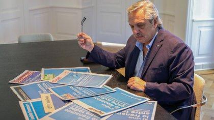 Alberto Fernández lee la tapa de todos los diarios nacionales que coordinaron una campaña para alertar sobre la pandemia del coronavirus